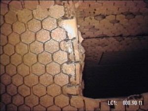 This image shows damaged bull-nose refractory at the cross over duct in a cyclone rector. A robotic pan & tilt camera was used for this application. The camera's ability to navigate and freely scan was vital to conducting an inspection of this area of the reactor.