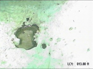 This is an image of an isolated area at the bottom elbow of a injection line with coating damages and internal corrosion. If you look closely, you can see the epoxy coating lifted at the edges around the deep corrosion pit. Some deposits are noticeable in the pit.
