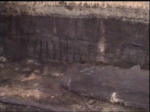 This image was captured using a large PTZ camera to inspect and record general conditions inside a drained sulphur pit. Exposed rebar is apparent on the wall of the pit.