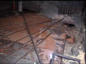 This sulphur pit has been emptied,  revealing the steam coils and other internal piping for inspection.