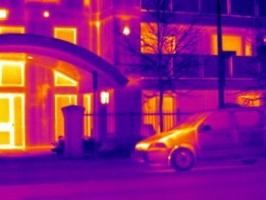 This image shows air leakage in a wood-framed, multi-story building under positive pressure.