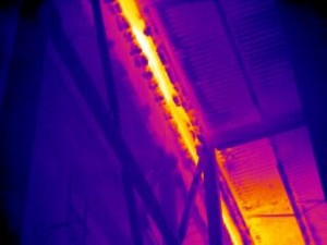 This image shows warm air infiltration between a pre-existing building and a freezer expansion that was added later. Moisture from the warm air is condensing and freezing on the cold surfaces around the envelope leak